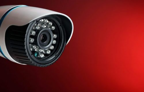 Security CCTV camera on red background, closeup
